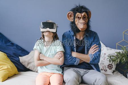 father wearing monkey mask sitting next