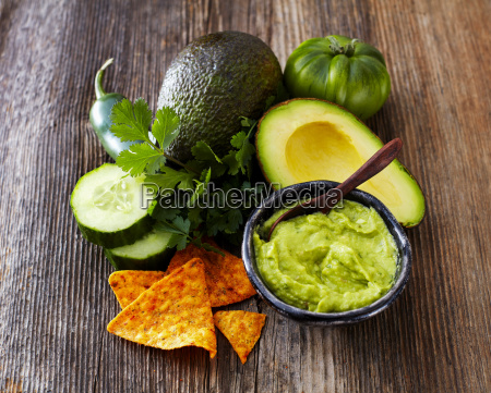bowl of guacamole ingredients and tortilla