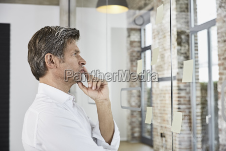 mature businessman looking at sticky notes