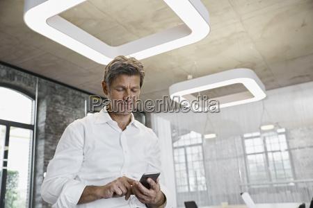 mature businessman using smartphone in modern