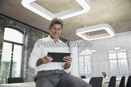 mature businessman using tablet in modern