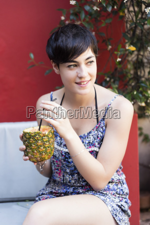 smiling young woman drinking a cocktail