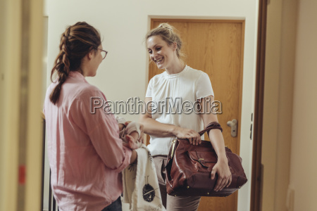 woman greeting midwife at her homes