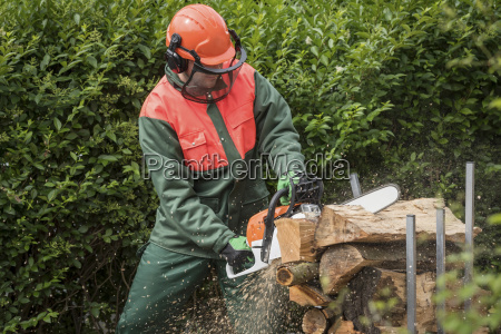 man wearing protective clothes sawing wood