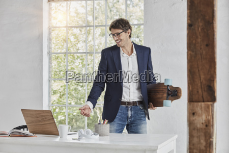 laughing businessman with skateboard looking at