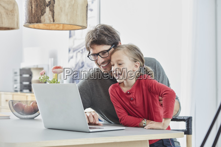 happy father and daughter using laptop