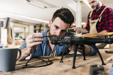 man working on drone in workshop