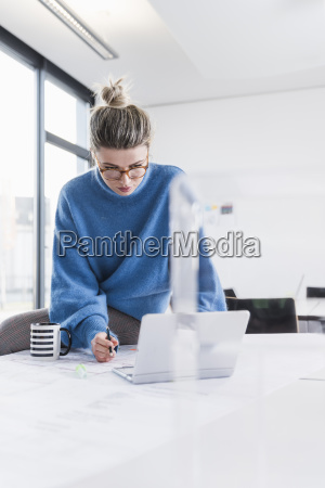 young woman with laptop and plan