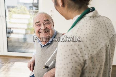 senior man smiling at nurse at