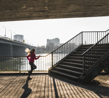 young woman running towards stairs at