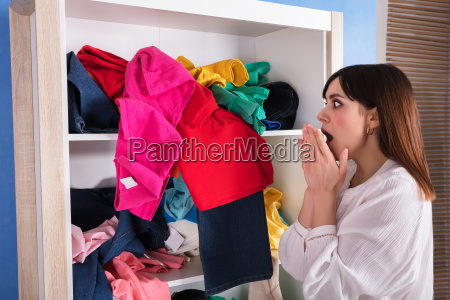 shocked, woman, looking, at, scattered, clothes - 24734548