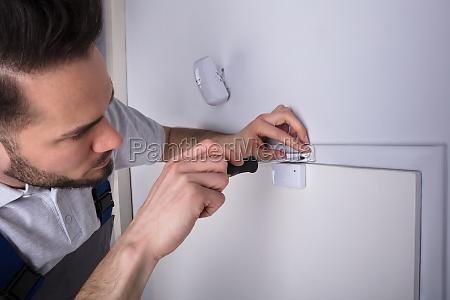 technician installing security system door sensor