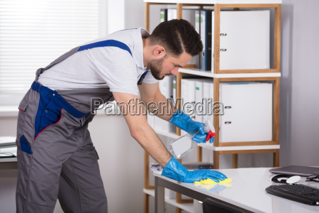 man cleaning desk in office