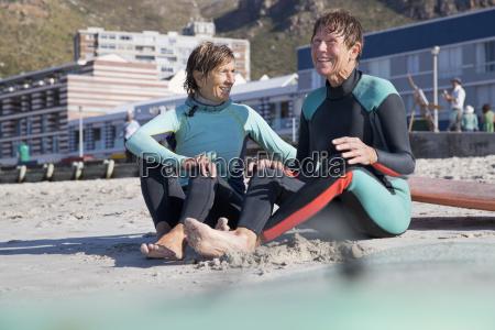 senior surfing friends sitting on beach