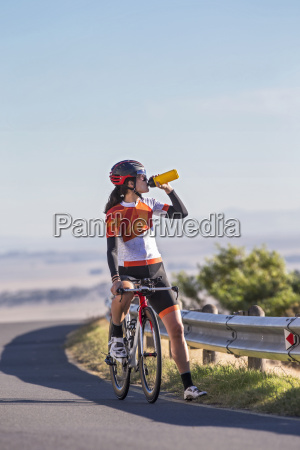 female cyclist taking drink from water