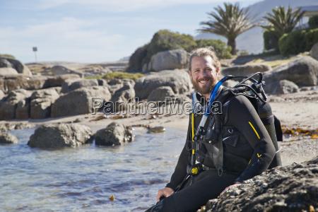 man in wetsuit going ocean scuba