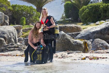 couple preparing scuba equipment for a