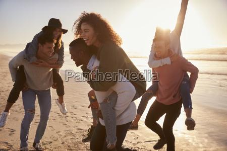 group of friends having piggyback race