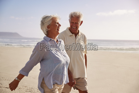 senior retired couple walking along beach
