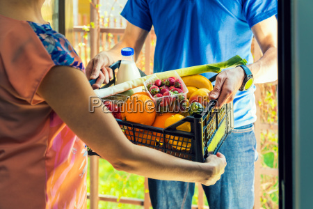 woman accepting groceries box from delivery