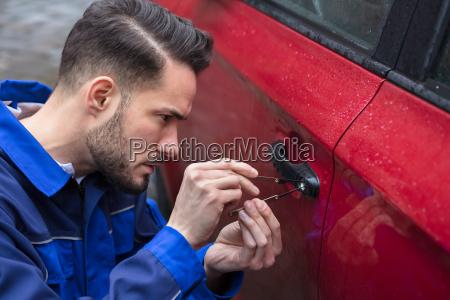 man opening car door with lockpicker