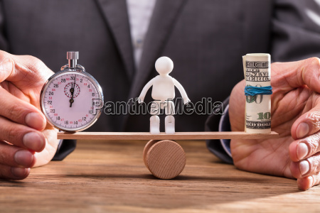 businessperson balancing stopwatch and banknotes