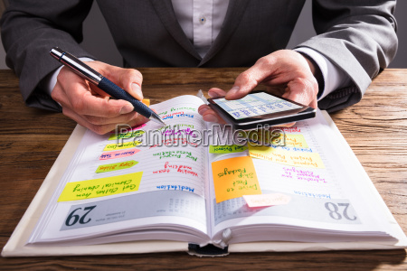 businessperson writing schedule in diary