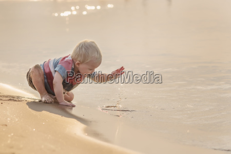 baby boy playing with water while