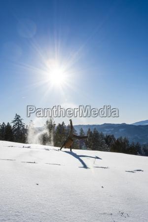 man doing cartwheel on snowy field