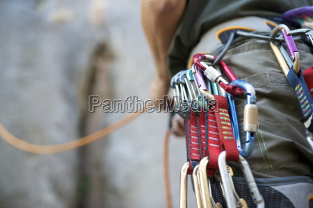 midsection of man with climbing equipment