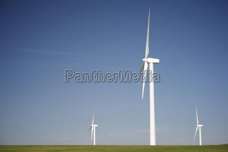 windmills on grassy field against blue