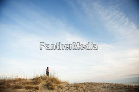 woman standing on beach against cloudy