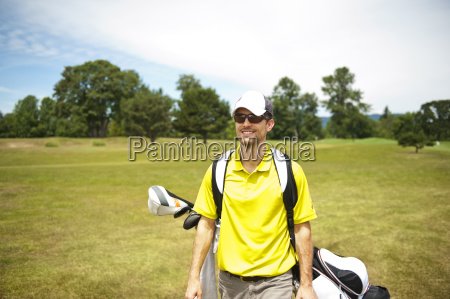 happy man holding golf bag and