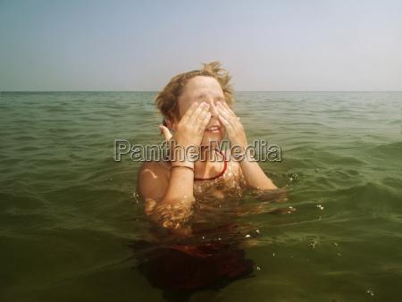 boy covering eyes in sea against