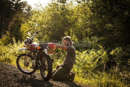 man repairing motorcycle while kneeling on