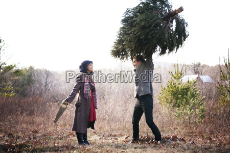 man carrying pine tree while woman