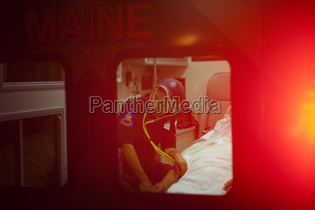 paramedic examining patient with stethoscope in