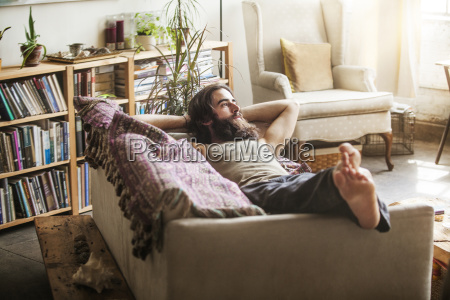 thoughtful man relaxing on sofa at