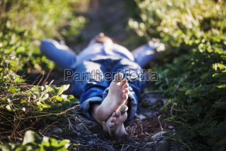 man lying on field at farm