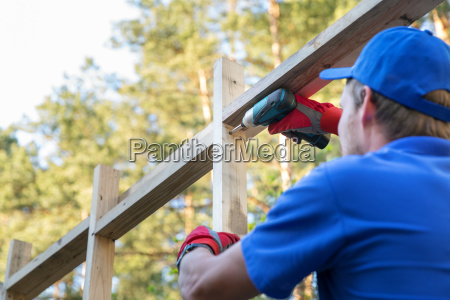 construction worker working on wooden house