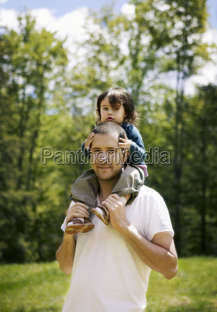 portrait of man carrying girl on