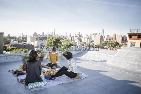 friends enjoying food on building terrace