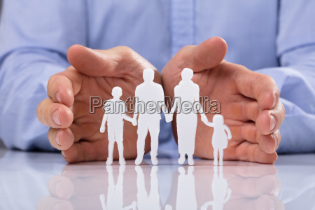 businessperson protecting family paper cut out