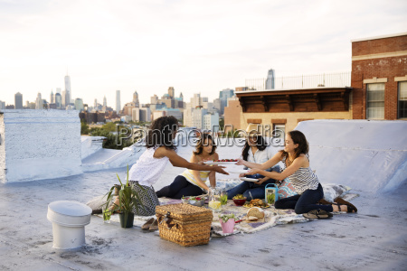 friends having food on building terrace