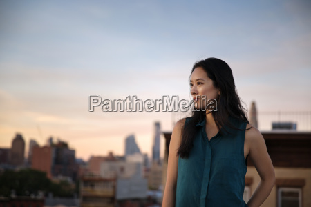 thoughtful woman standing on building terrace