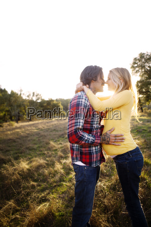 man with pregnant partner standing on