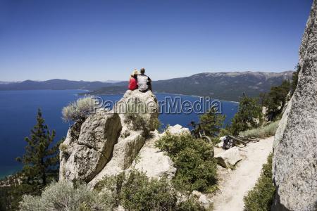 couple sitting on cliff overlooking lake