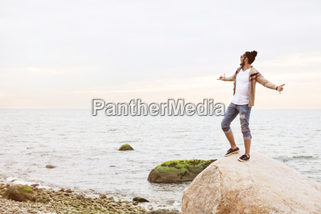 man standing on rock with arms