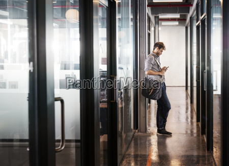 man using mobile phone while leaning