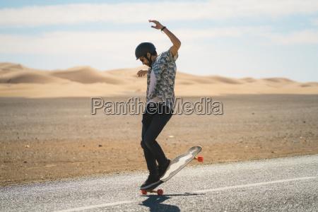 man skateboarding on road during sunny